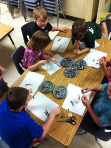 Students adding wire and beads to their teapot ornaments